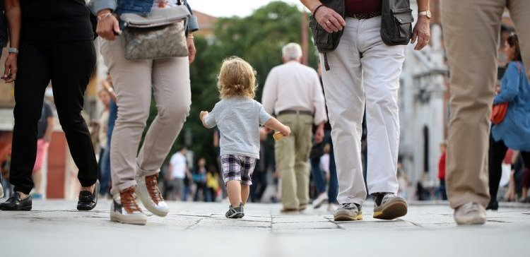 Photo back view of cute fair-haired blond kid tiny little child baby boy holding bun in hand walking along flag-stone pavement in crowd cityscape on blurred grey background, horizontal picture