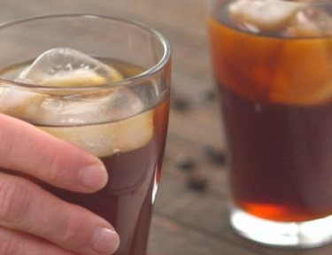 Hand holding a glass of cold brew coffee next to another glass