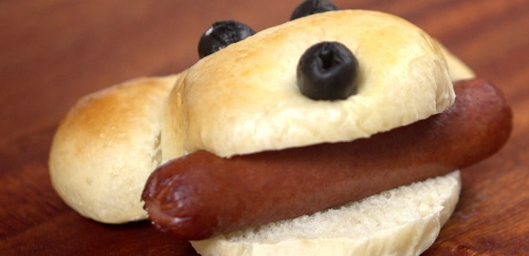 Close-up of a single hot dog in bun shaped liked dog