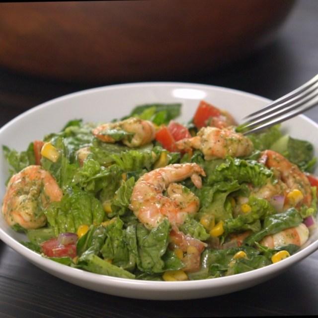 Fork descending on salad of shrimp, avocado and corn