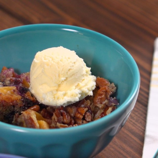 Scoop of peach blueberry dump cake in bowl with vanilla ice cream