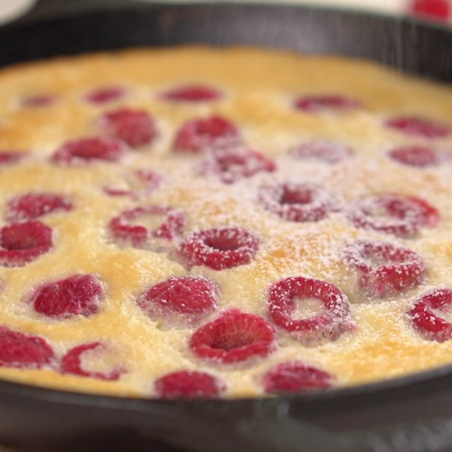 Sprinkling powdered sugar on baked raspberry clafoutis