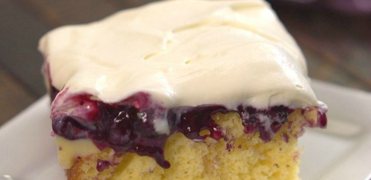 Piece of lemon pudding cake topped with blueberry sauce and cream cheese frosting