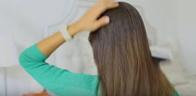 Brush hair back to prepare for ponytail trick