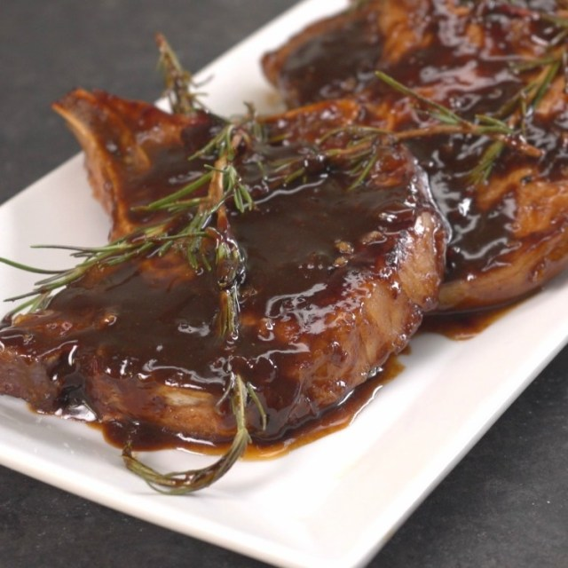Honey balsamic glazed pork chops on a white plate