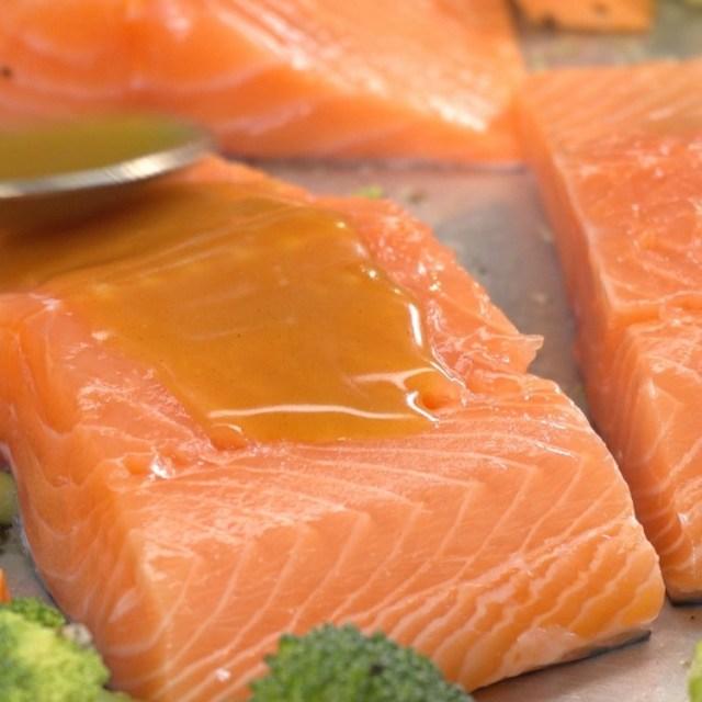 Spooning honey glaze over sheet pan salmon