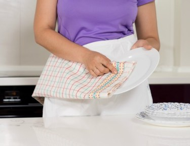 Woman drying dishes with kitchen towel.