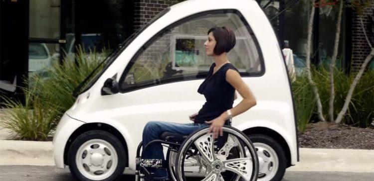 Picture of woman sitting next to wheelchair friendly electric car.