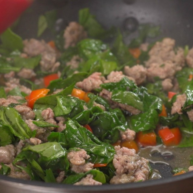 Frying breakfast sausage, spinach and pepper for breakfast taquito filling
