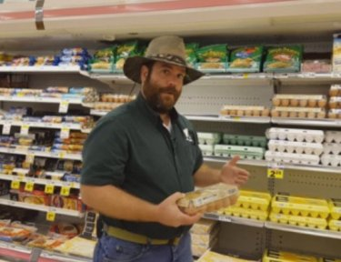 man stands holding a carton of eggs at a grocery store