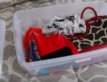 clothing and accessories in plastic bin
