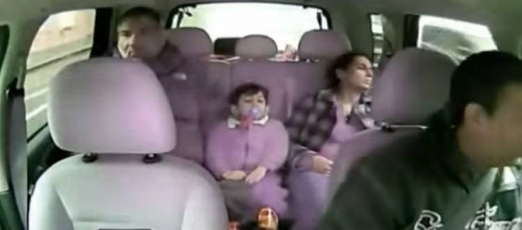 family in the backseat of a taxi