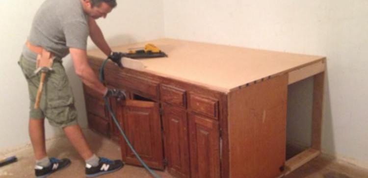 Man sands down cabinets