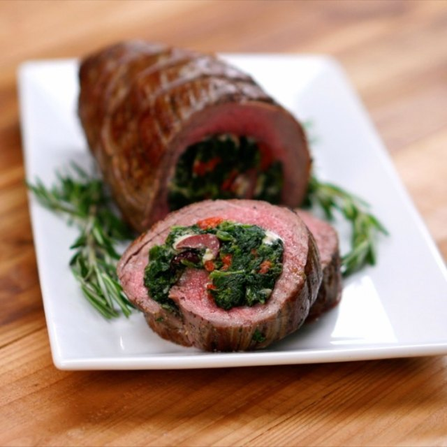Flank steak roulade on white plate