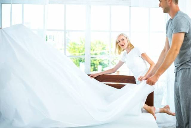 blond woman and tall man make bed