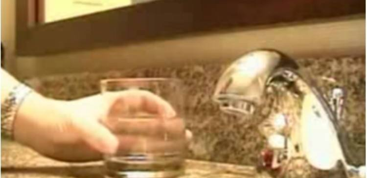 person holding drinking glass by sink