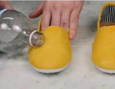 person pouring water on yellow shoe