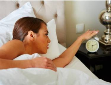 woman in bed turning off alarm clock