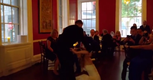 Groom accidentally trips bride during their first dance.