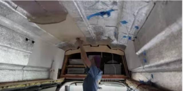 Christine adding insulation to the roof of her van