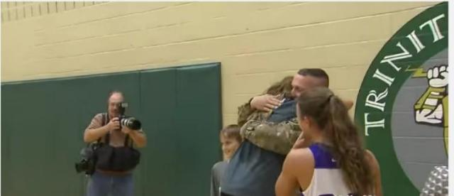 MacKenzie hugs her soldier dad in a gym
