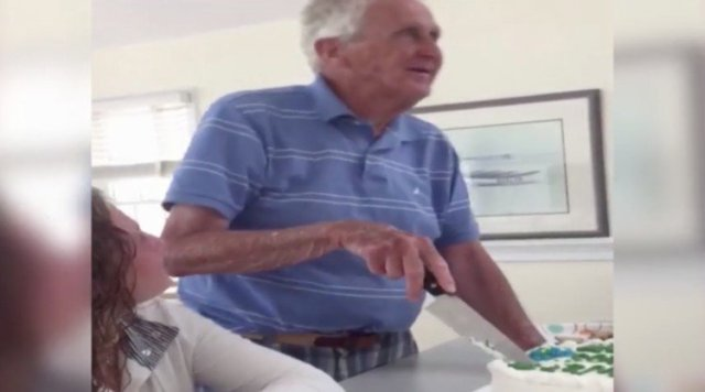 Grandpa struggles to cut his birthday cake.