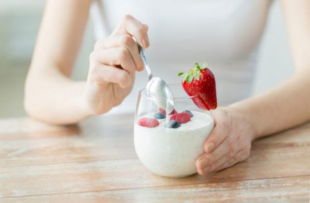 Woman eats yogurt with fresh fruit.