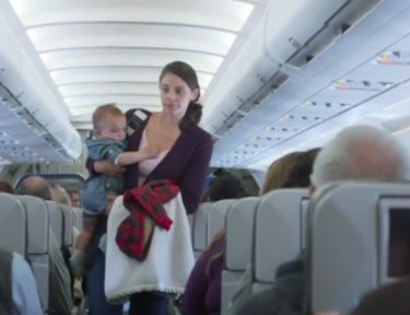 mother carrying a baby down an airplane aisle