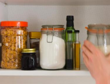 person reaching for various pantry items