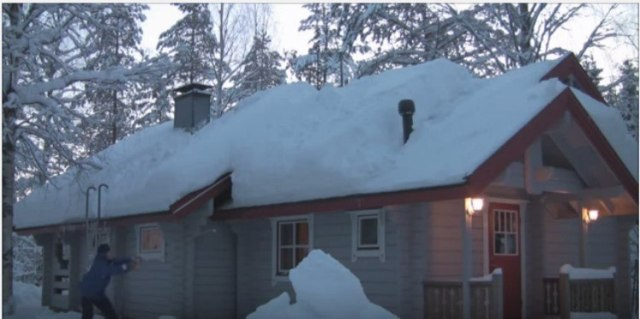 person removing snow from roof with a string