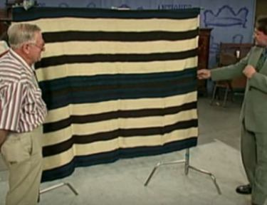 man and appraiser standing next to Navajo blanket
