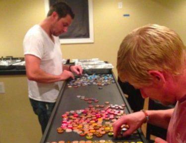 two men placing bottle caps on countertop