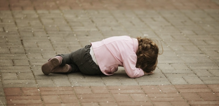 Image of girl lying on pavement.