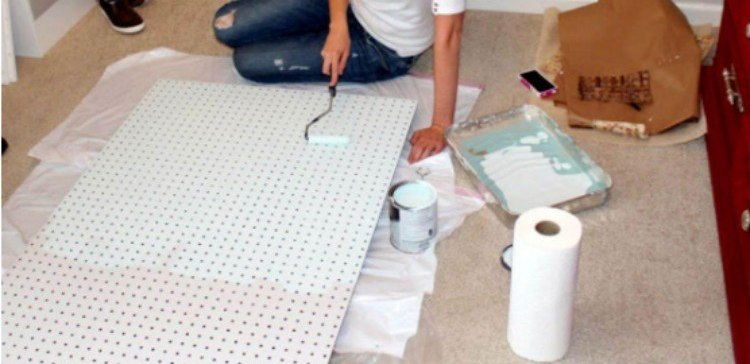 woman painting a pegboard white