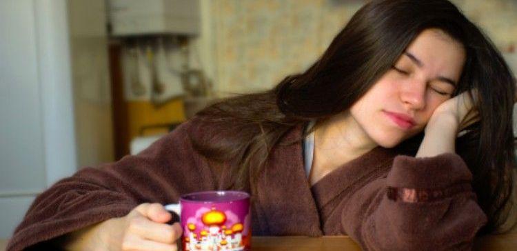 sleeping woman in robe holding coffee mug