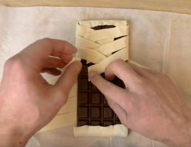 Folding pastry around a full chocolate bar.