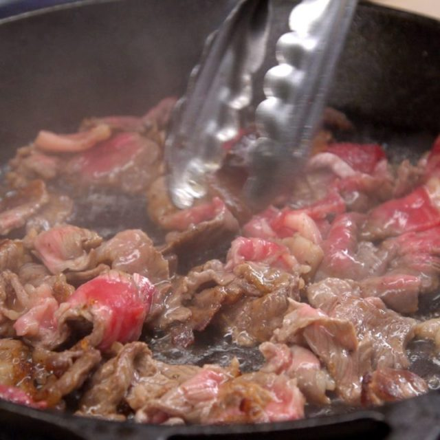Philly Cheesesteak Sliders sauteeing the thinly sliced ribeye steak