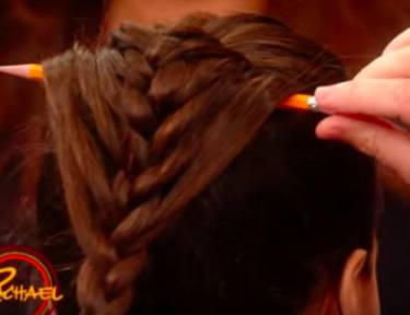 person holding pencil in braid