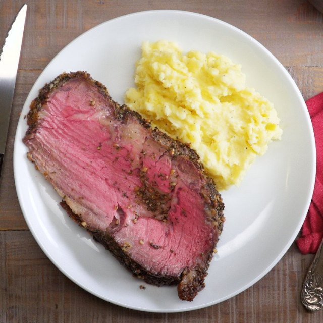 Herb and Garlic Prime Rib Roast slice on plate with mashed potatoes
