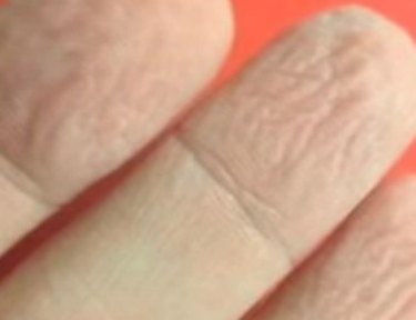 wrinkly fingers against orange background