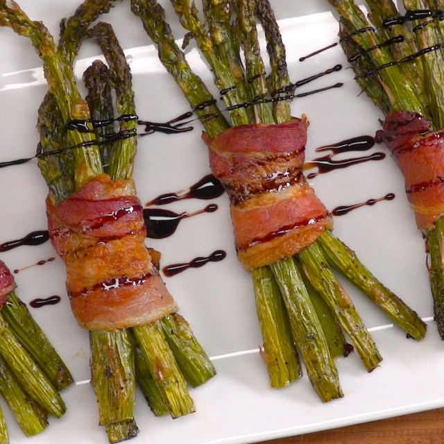 Easy elegant appetizer to make your next dinner party extra fancy: crispy roasted asparagus spears bundled in bacon and drizzled with honey balsamic glaze.