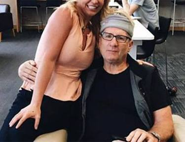 Ed O'Neill taking a picture with a fan.