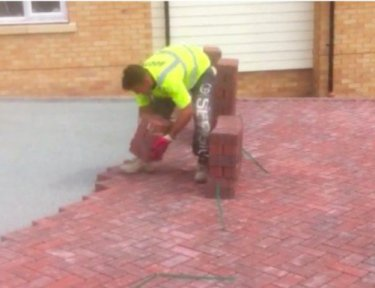 bricklayer setting bricks down on patio