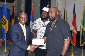 "Culture Minister, Stephen Lashley presents Darin Holder with his BDS $10,000 cheque for winning the CARIFSTA XIII jingle competition. Looking on is music producer Dwain ""Dwaingerous"" Antrobus who assisted in the production of the jingle. (Photo by A.Miller via BGIS)"