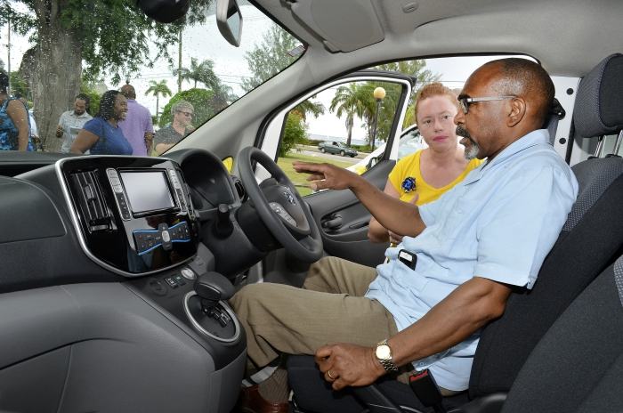 Managing Director of Mega Power Limited, Joanna Edgehill, showing Minister with responsibility for Energy, Senator Darcy Boyce, the features of one of the electric vehicles yesterday. (W.Alleyne/BGIS)