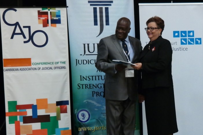 The Honourable Sir Marston Gibson, Chief Justice of Barbados receives a copy of the Model Guidelines for Sexual Offence Cases in the Caribbean Region from the Honourable Mme. Justice Maureen Rajnauth-Lee, Judge of the Caribbean Court of Justice at the launch of the Guidelines at the CAJO Conference in Curacao. (Photo via CCJ)