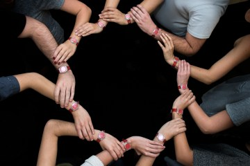 To convey a team effort, students lock arms in a circle to showcase their red watches, which signal they can intervene in risky situations related to drugs and alcohol.