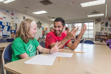 "Leah Reed, 10 (left), learns how to write in Arabic from CAVE Volunteer Yahya ""John"" Al Maqboul (right) at the Boys & Girls Club on Monday, March 21, 2016 in Chico, Calif."