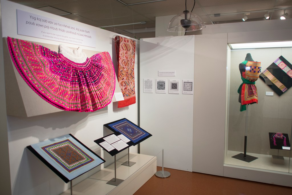 "Several colorful, traditional Hmong garments on display at the ""Hmong Reflections: Stories of Our Own"" exhibit."