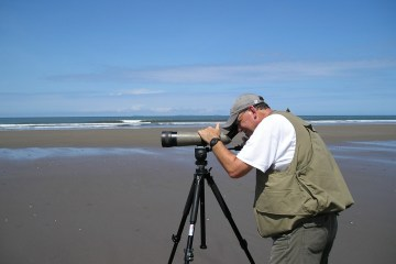 Jay Bogiatto watches birds through a scope on a beach in Panama.